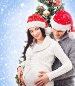 Young pregnant woman and happy father decorating Christmas tree over blue background with snow