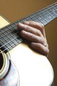Hand auf akustische Gitarre