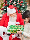 Santa Claus giving gift to girl in front of Christmas tree