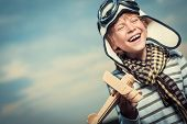 Laughing boy with plane on the background of sky