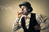 funny clown with bowler hat smokes a cigar