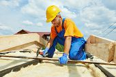 stock photo of girder  - construction roofer carpenter worker hammering wood board with hammer and nail on roof installation work - JPG