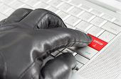 Online Illegal Download With Hand Wearing Black Leather Glove Pressing Enter Key