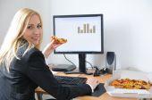 Pessoa de negócios que comer Pizza no trabalho