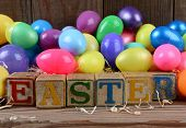 The word Easter spelled out in childrens toy blocks and a pile of plastic eggs. Horizontal format on a rustic wood background.