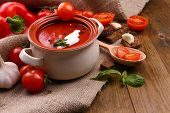 Tasty tomato soup and vegetables on wooden table