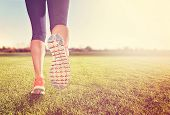 an athletic pair of legs on grass during sunrise or sunset - healthy lifestyle concept