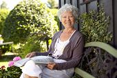 pic of sitting a bench  - Happy senior woman sitting on bench in her backyard garden with a newspaper looking at camera smiling - JPG