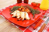 meat grilled chicken fillet with salad and tomatoes on red plate over wooden table with cutlery on l