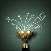 pic of champagne color  - First place championship trophy or cup in front of blackboard with champagne and fireworks concept for winning and success - JPG
