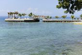 A beautiful palm-studded pier with a walking bridge to a gazebo, all jutting out into the pristine waters of the Caribbean.  Plenty of space for your text on watery foreground.