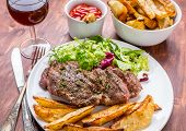 Grilled Rib-eye Beef Steak with Green Salad and Herb Potato Wedges