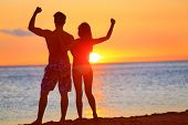 Sporty fitness couple cheering at beach sunset. Happy romantic fit young couple enjoying sunset with
