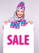Woman In Winter Outerwear  Holds The White Banner With Sale Word On It
