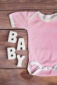 word baby and child clothing on wood background