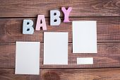 word baby and white frame photo on wood background