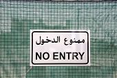 picture of no entry  - No Entry sign in English and Arab on green chain link fence in front of A construction place - JPG