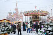 MOSCOW, RUSSIA - DEC 8, 2013: People walk near carousel and St. Basil cathedral during Christmas fai