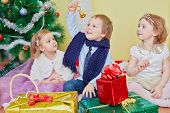 Three children sit on furry rug under christmas tree, boy rings hand bell which he holds in his hand