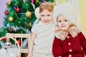 Two little girls sit embracing on wooden chair in room with decorated christmas tree