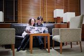 Pretty woman and man sit at sofa in hall with newspaper and smile