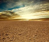 image of plowed field  - Plowed farmland field on the background of cloudy sky in sunset rays