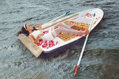 Romantic young Woman cuddling in rowboat at lake