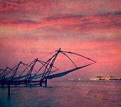 Vintage retro hipster style travel image of Kochi chinese fishnets on sunset. Fort Kochin, Kochi, Ke