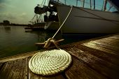 Coil of rope on the wooden pier tied up to the yacht. Focus on the coil.