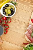 Red wine with olives, tomatoes, prosciutto, bread and spices. Over wooden table background. View fro