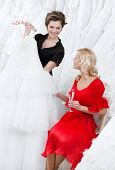 Shop assistant offers another dress to the bride while she is drinking champagne