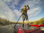 mature male paddler enjoying workout on an inflatable stand up paddleboard (SUP), calm lake in one o