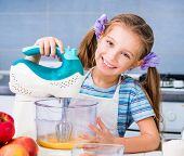 little cute girl with a mixer whisk the eggs in the kitchen at home