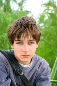 stock photo of teenage boys  - sad teenager sitting on the trees background - JPG