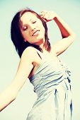 Happy young woman with raised hand during sunny day.