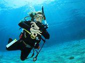 Young woman scuba diving signals