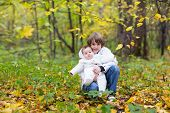 Brother Holding His Baby Sister Both In White Jackets In An Autumn Park With Yellow Trees
