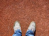 A Pair Of Feet Standing On A Running Track Rubber With Space For Print Of The Text.