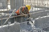 A construction workers hacking concrete beam