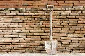 Shovel On Red Brick Wall Background.