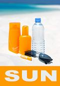 Sunglasses, Water And Sun Protection Cream On Beach Background