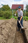 Farmer Digging The Earth To Build A Deep Bed Of