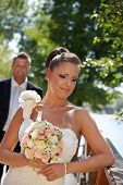 Outdoor portrait of beautiful young bride in wedding gown.