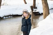 Cute Boy Walking Along A Frozen Brook On A Sunny Winter Day