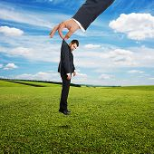 big hand holding small sad businessman over green field and blue sky