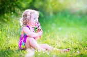 picture of vanilla  - Funny happy toddler girl with curly hair wearing pink colorful summer dress sitting on a green lawn eating vanilla and chocolate ice cream cone in a sunny garden or park - JPG