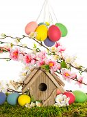 Easter Decoration With Birdhouse And Eggs On Green Grass