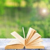 Open book on table outdoors