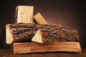 Heap of firewood on floor on dark background