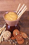Fondue, spice, biscuits on wooden background